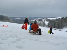 Kinder beim Schlittenfahren im Schnee